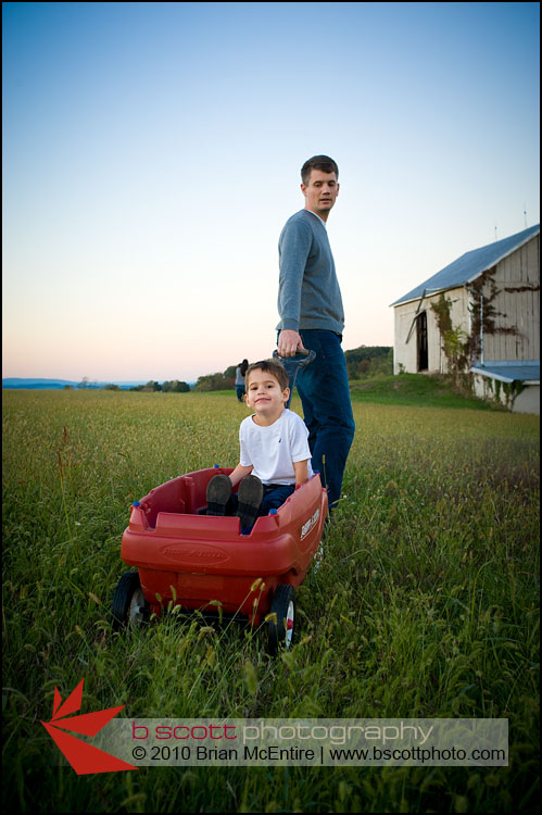 Father pulls his son through a grassy field after sunset in Frederick, MD.