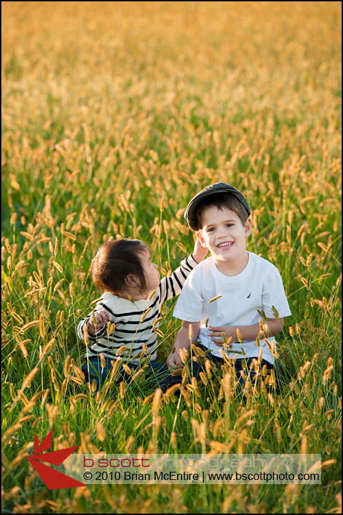 Two young children play in a beautiful field at sunset in Frederick, MD.