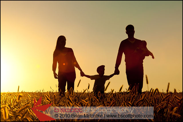 Family walks through grassy field in Frederick, MD, silhouetted by setting sun.