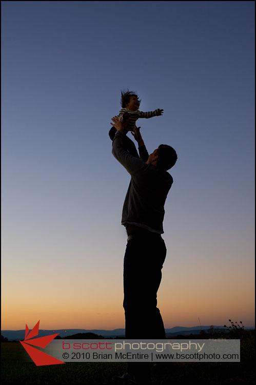 Father lifts young baby girl into a sky filled with rich colors.