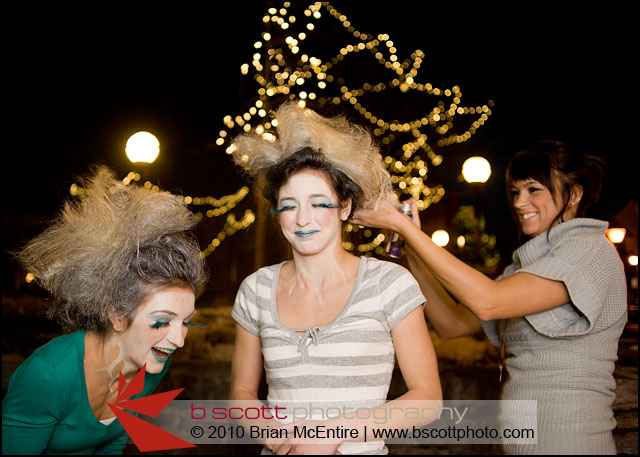 Model assisting and having fun spraying hair