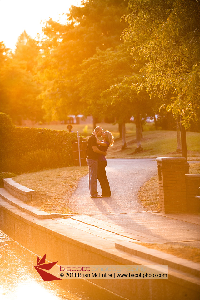 Couple kisses with strong sun flare along river walk path.