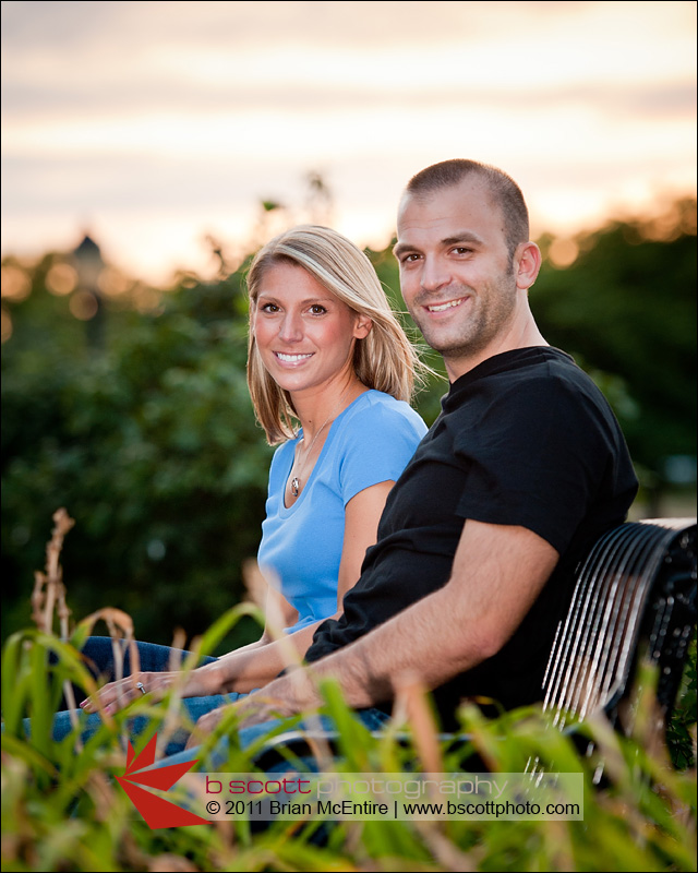 Handsome couple sits at bench in Baker Park, Frederick, MD during sunset.
